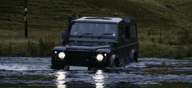 A Land Rover Defender going off-road in a river