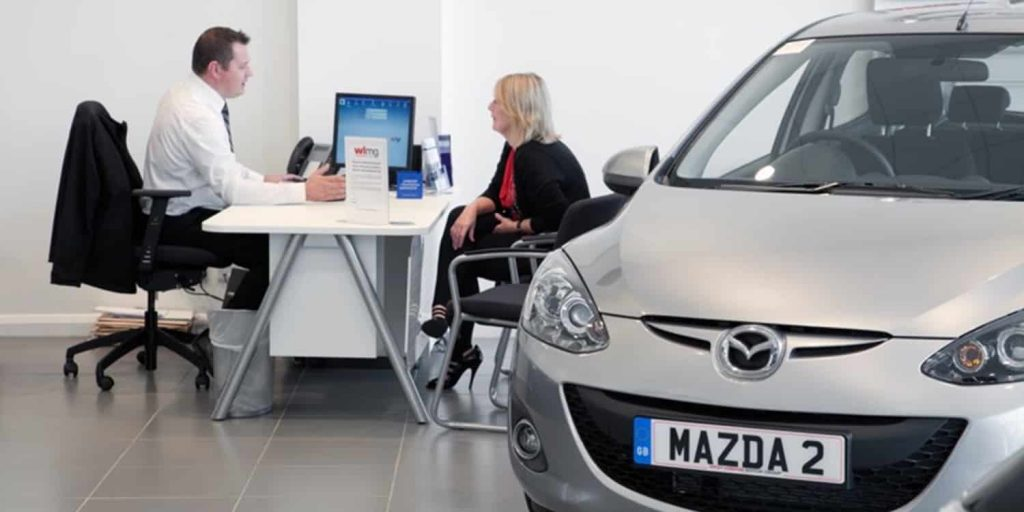 Discussing car finance, like a hire purchase or PCP, in a car showroom
