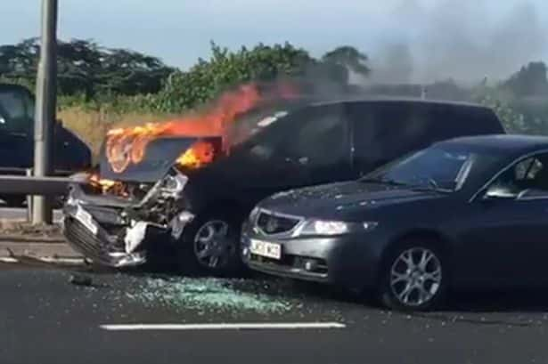 An Uber cab in flames after an accident