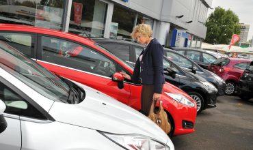 Car buyer on dealer forecourt looking at diesel car