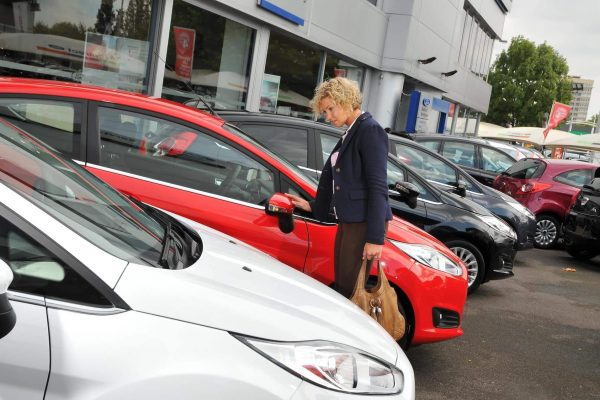 Car buyer on dealer forecourt looking at diesel car