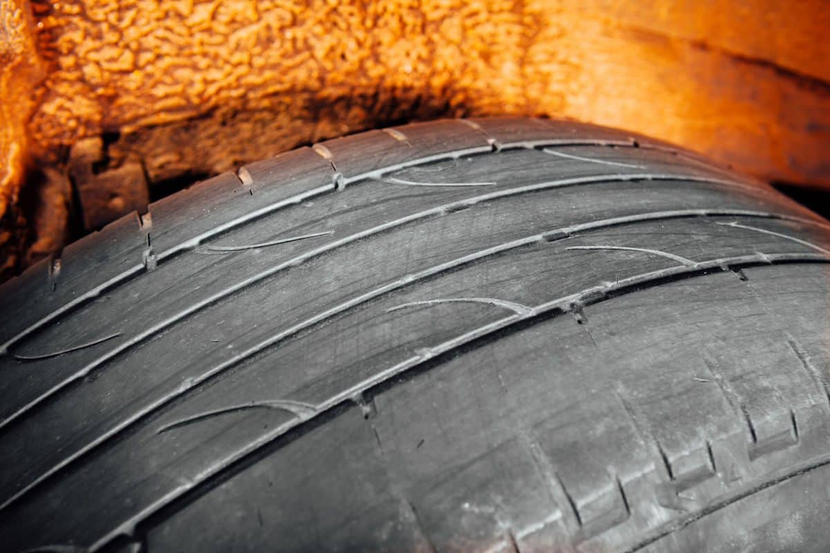 Worn tyre with tread-depth markers showing