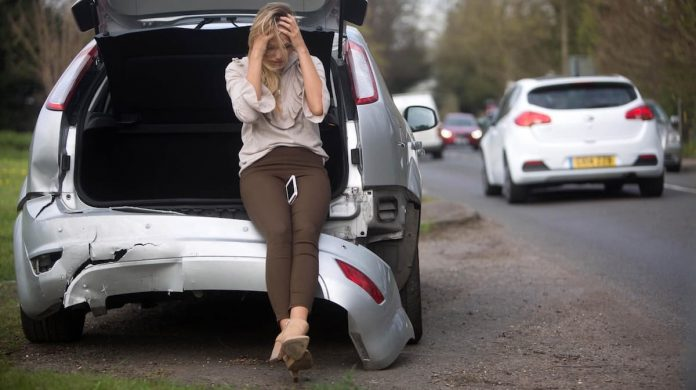 Young woman driver with a car insurance write-off
