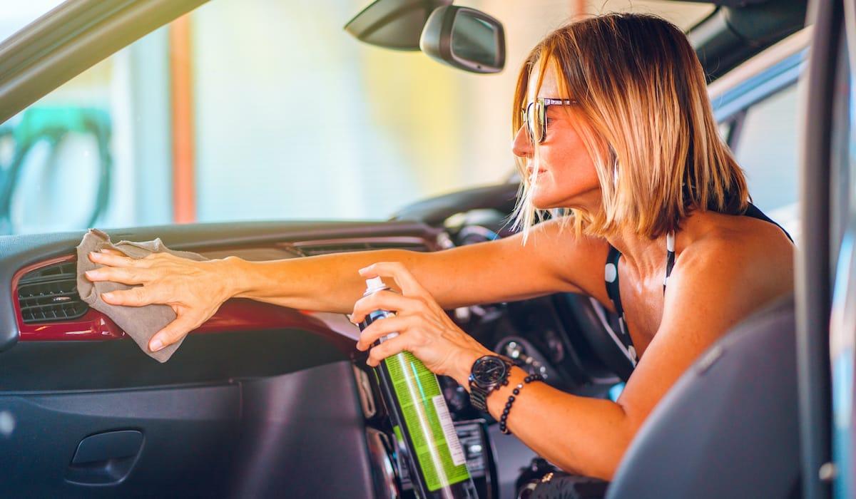 woman cleaning car dashboard